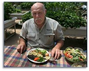 Murray Hallam dining with his aquaponic systems